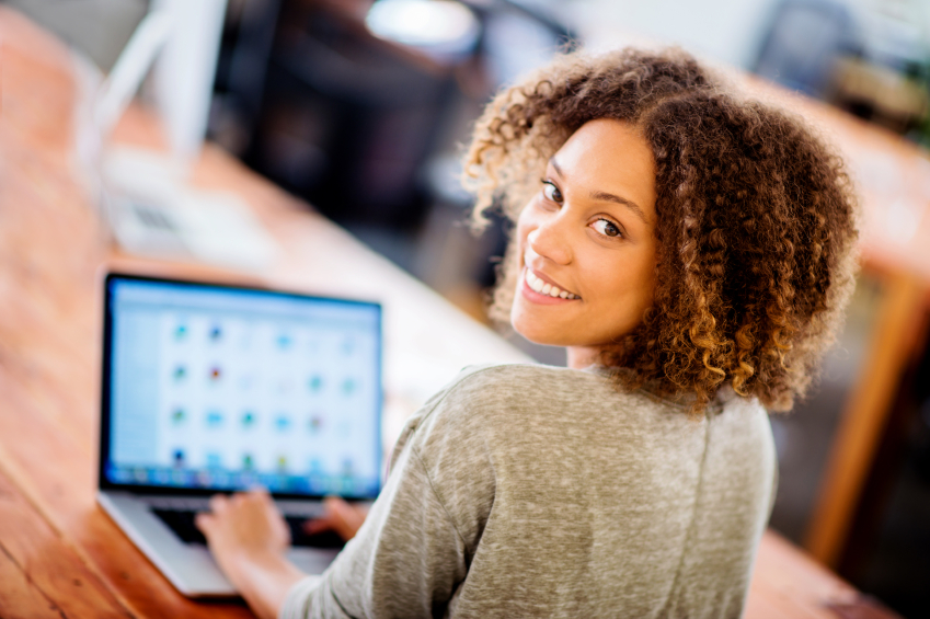 Young woman sits at computer screen