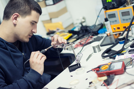 Trainee is soldering in workshop