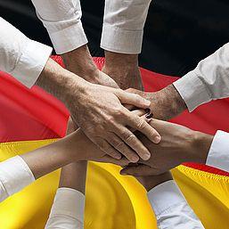 Hände zusammen auf deutsche Flagge