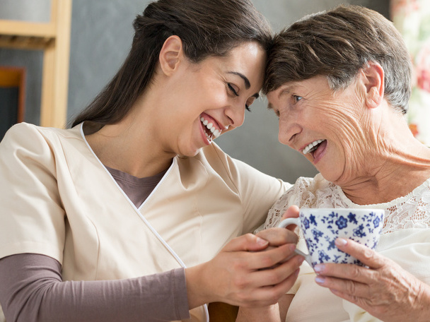 Geriatric nurse drinks tea with patient