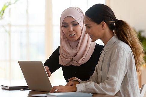 Muslim female teaching a woman computer work
